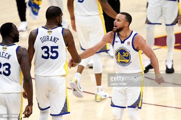 Stephen Curry and Draymond Green of the Golden State Warriors celebrate with Kevin Durant against the Cleveland Cavaliers in the second half during...