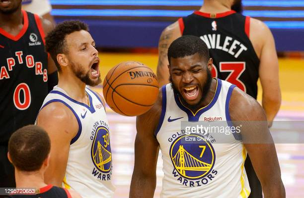 Stephen Curry and Eric Paschall of the Golden State Warriors react after Paschall made a shot and was fouled during their game against the Toronto...