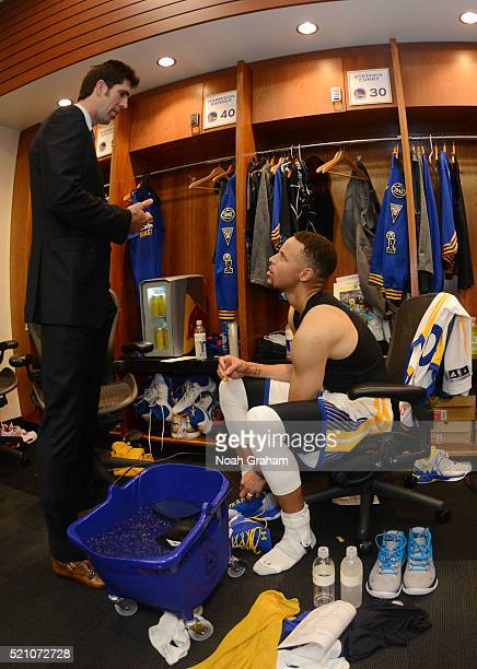 Stephen Curry and Golden State Warriors General Manager Bob Myers talk in the locker room after the game against the Memphis Grizzlies on April 13...