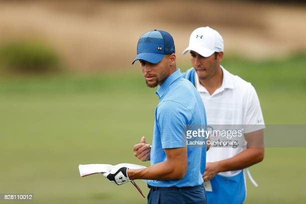 Stephen Curry and his caddie Jonnie West check their yardage on the fifteenth hole during round one of the Ellie Mae Classic at TCP Stonebrae on...
