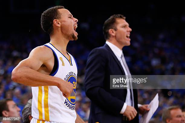 Stephen Curry and interim head coach Luke Walton react from the bench to a play against the New Orleans Pelicans during the NBA season opener at...
