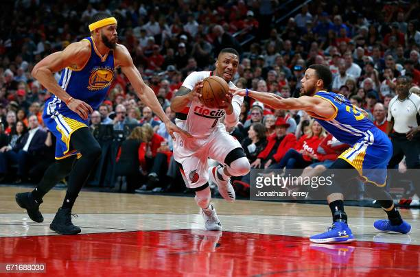 Stephen Curry and JaVale McGee of the Golden State Warriors defend Damian Lillard of the Portland Trail Blazers during Game Three of the Western...