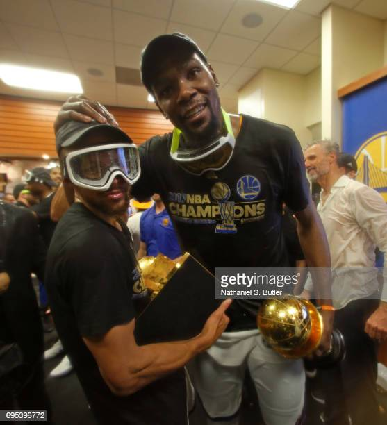 Stephen Curry and Kevin Durant of the Golden State Warriors celebrates and holds the Larry O'Brien Trophy and the Bill Russell Finals MVP Trophy in...