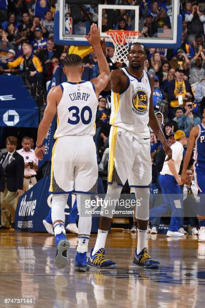 Stephen Curry and Kevin Durant of the Golden State Warriors exchange high fives during the game against the Philadelphia 76ers on November 11 2017 at...