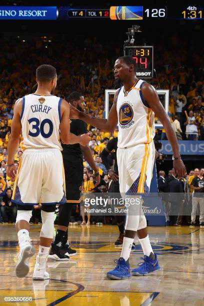 Stephen Curry and Kevin Durant of the Golden State Warriors high five against the Cleveland Cavaliers in Game Five of the 2017 NBA Finals on June 12...