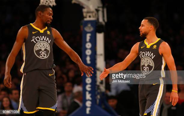 Stephen Curry and Kevin Durant of the Golden State Warriors in action against the New York Knicks at Madison Square Garden on February 26 2018 in New...