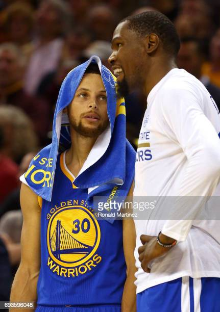 Stephen Curry and Kevin Durant of the Golden State Warriors look on from the bench in the second quarter against the Cleveland Cavaliers in Game 3 of...