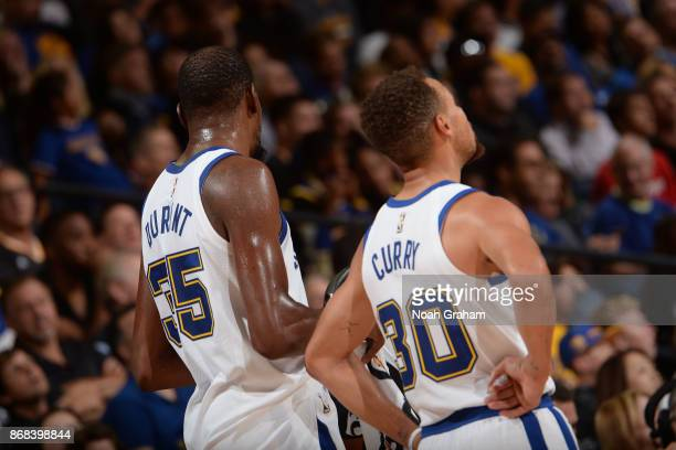 Stephen Curry and Kevin Durant of the Golden State Warriors looks on during the game against the Washington Wizards on October 27 2017 at ORACLE...