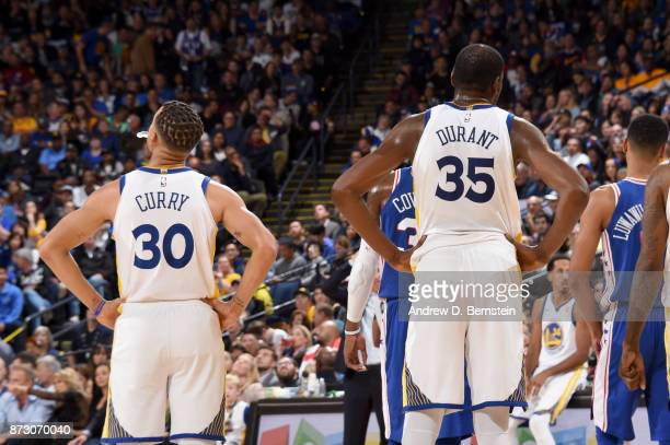 Stephen Curry and Kevin Durant of the Golden State Warriors looks on during the game against the Philadelphia 76ers on November 11 2017 at ORACLE...