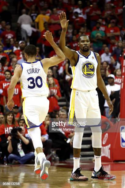 Stephen Curry and Kevin Durant of the Golden State Warriors react late in the game against the Houston Rockets in Game One of the Western Conference...