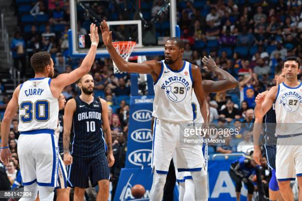Stephen Curry and Kevin Durant of the Golden State Warriors react during game against the Orlando Magic on December 1 2017 at Amway Center in Orlando...