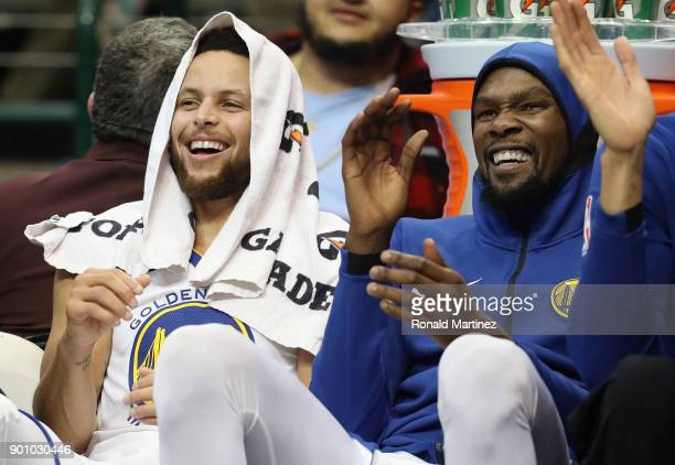 Stephen Curry and Kevin Durant of the Golden State Warriors share a laugh during play against the Dallas Mavericks at American Airlines Center on...