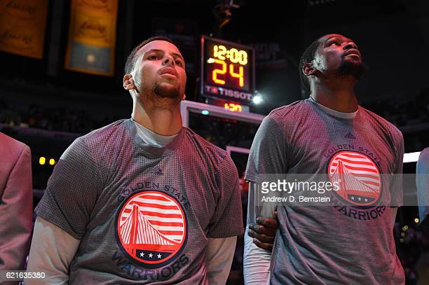 Stephen Curry and Kevin Durant of the Golden State Warriors stand on the court for the National Anthem before the game against the Los Angeles Lakers...