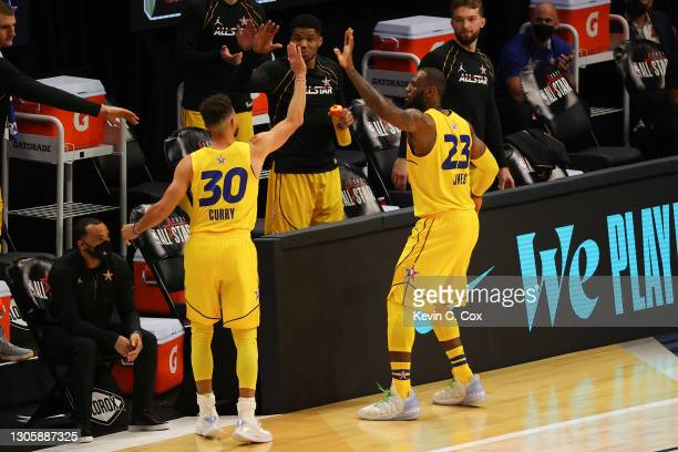 Stephen Curry and Lebron James of Team LeBron react during the first half against Team Durant in the 70th NBA All-Star Game at State Farm Arena on...
