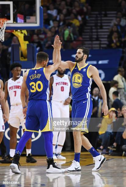 Stephen Curry and Omri Casspi of the Golden State Warriors high five each other after a score against the Detroit Pistons during an NBA basketball...