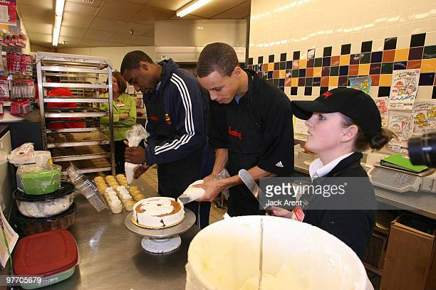 Stephen Curry and Reggie Williams of the Golden State Warriors put icing on a cake during the Warriors Great American Bake Sale presented by Lucky's...