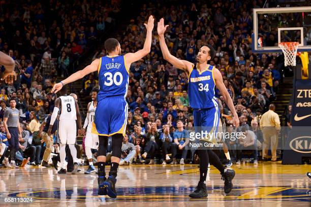Stephen Curry and Shaun Livingston of the Golden State Warriors highfive during the game against the Memphis Grizzlies on March 26 2017 at ORACLE...