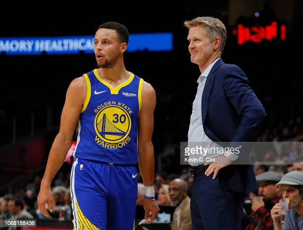 Stephen Curry and Steve Kerr of the Golden State Warriors converse against the Atlanta Hawks at State Farm Arena on December 3 2018 in Atlanta...