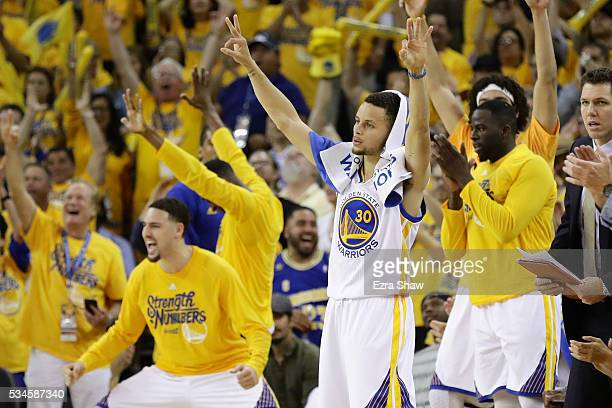 Stephen Curry and the bench of the Golden State Warriors react to a score against the Oklahoma City Thunder during Game Five of the Western...