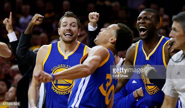 Stephen Curry celebrates with David Lee and Festus Ezeli of the Golden State Warriors as the defeated the Cleveland Cavaliers 105 to 97 during Game...