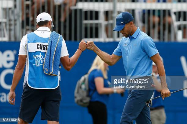 Stephen Curry celebrates with his caddie Jonnie West after a par on the eighteenth hole during round one of the Ellie Mae Classic at TCP Stonebrae on...