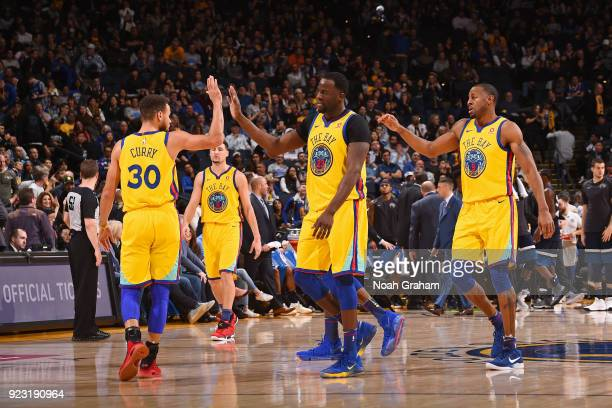 Stephen Curry Draymond Green and Andre Iguodala of the Golden State Warriors give high fives during the game against the Minnesota Timberwolves on...