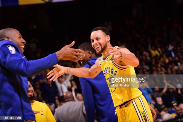 Stephen Curry hifives Andre Iguodala of the Golden State Warriors on March 21 2019 at ORACLE Arena in Oakland California NOTE TO USER User expressly...