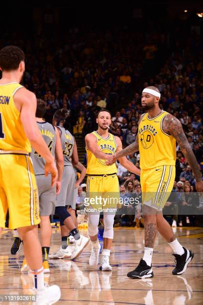 Stephen Curry hifives DeMarcus Cousins of the Golden State Warriors on March 21 2019 at ORACLE Arena in Oakland California NOTE TO USER User...