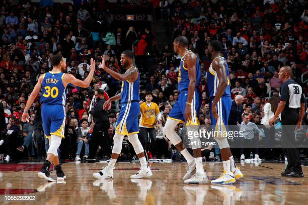 Stephen Curry high fives Alfonzo McKinnie of the Golden State Warriors during the game against the Chicago Bulls on October 29 2018 at United Center...