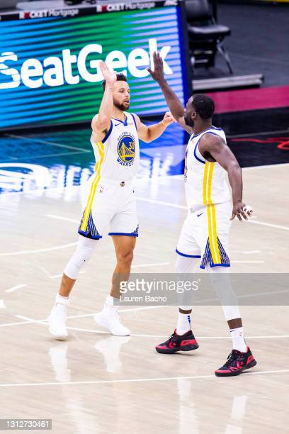 Stephen Curry high fives Draymond Green of the Golden State Warriors during the fourth quarter of a game against the Cleveland Cavaliers at Rocket...