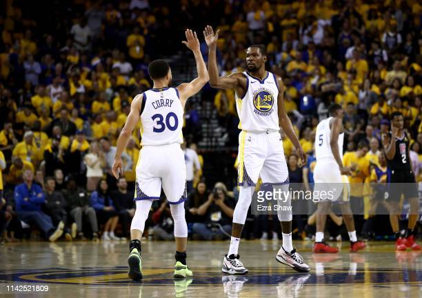 Stephen Curry high fives Kevin Durant of the Golden State Warriors during their game against the LA Clippers during Game One of the first round of...