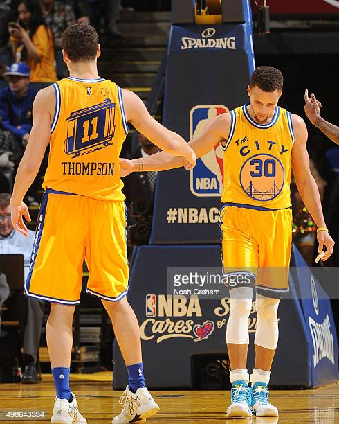 Stephen Curry high fives teammate Klay Thompson of the Golden State Warriors during the game against the Los Angeles Lakers on November 24 2015 at...