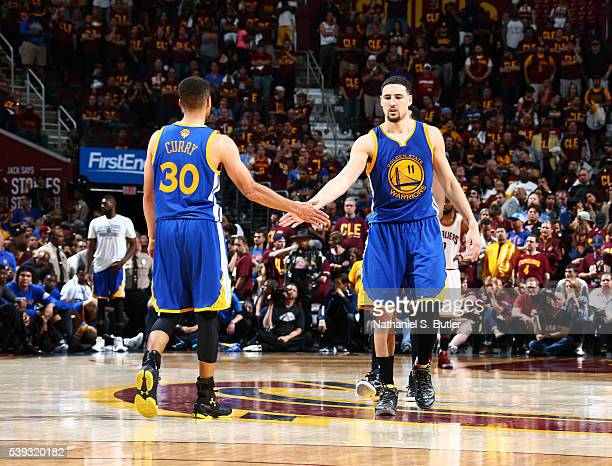 Stephen Curry high fives teammate Klay Thompson of the Golden State Warriors after a play against the Cleveland Cavaliers during Game Four of the...