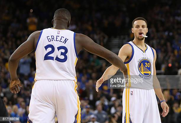 Stephen Curry highfives Draymond Green of the Golden State Warriors during their game against the Los Angeles Clippers at ORACLE Arena on March 23...