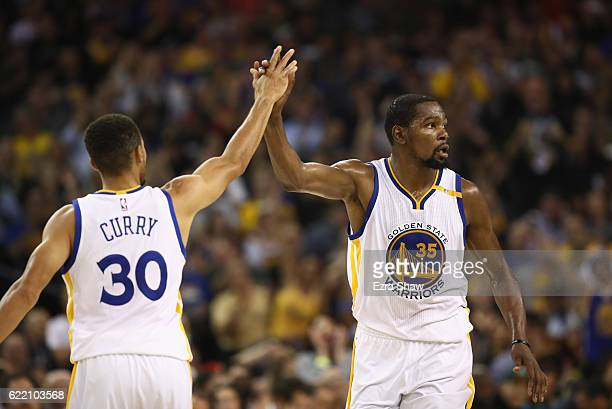 Stephen Curry highfives Kevin Durant of the Golden State Warriors during their game against the Dallas Mavericks at ORACLE Arena on November 9 2016...