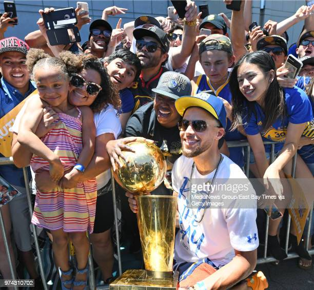 Stephen Curry holds the Larry O'Brien NBA Championship Trophy as he and his daughter Riley are photographed with fans during the Golden State...