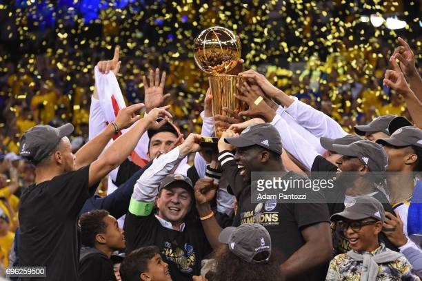 Stephen Curry Joe Lacob and Draymond Green of the Golden State Warriors celebrate with the Larry O'Brien Trophy on stage after winning Game Five of...