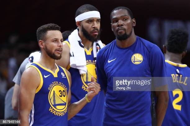 Stephen Curry Kevin Durant and JaVale McGee of the Golden State Warriors look on during react the game between the Minnesota Timberwolves and the...
