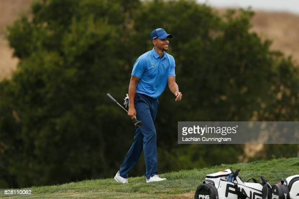 Stephen Curry laughs as he makes his caddie Jonnie West get his golf ball from the hole after scoring a birdie on the sixth hole during round one of...