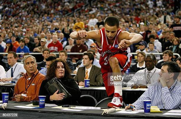 Stephen Curry of the Davidson Wildcats climbs up the scorer's table on to the court after he fell over it attempting to save the ball from going out...