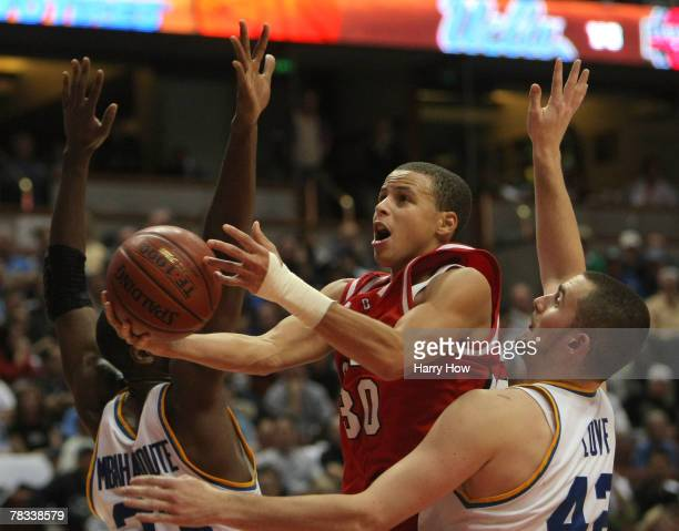 Stephen Curry of the Davidson Wildcats tries a layup between Luc Richard Mbah a Moute and Kevin Love of the UCLA Bruins during the second half of the...