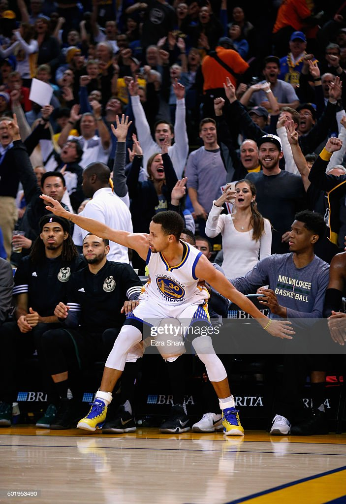 Stephen Curry #30 of the Golden State Warriors almost falls into the Milwaukee Bucks bench after he made a basket at ORACLE Arena on December 18, 2015 in Oakland, California.