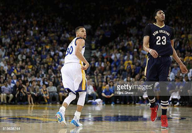 Stephen Curry of the Golden State Warriors and Anthony Davis of the New Orleans Pelicans watch a threepoint basket by Curry go in the basket at...
