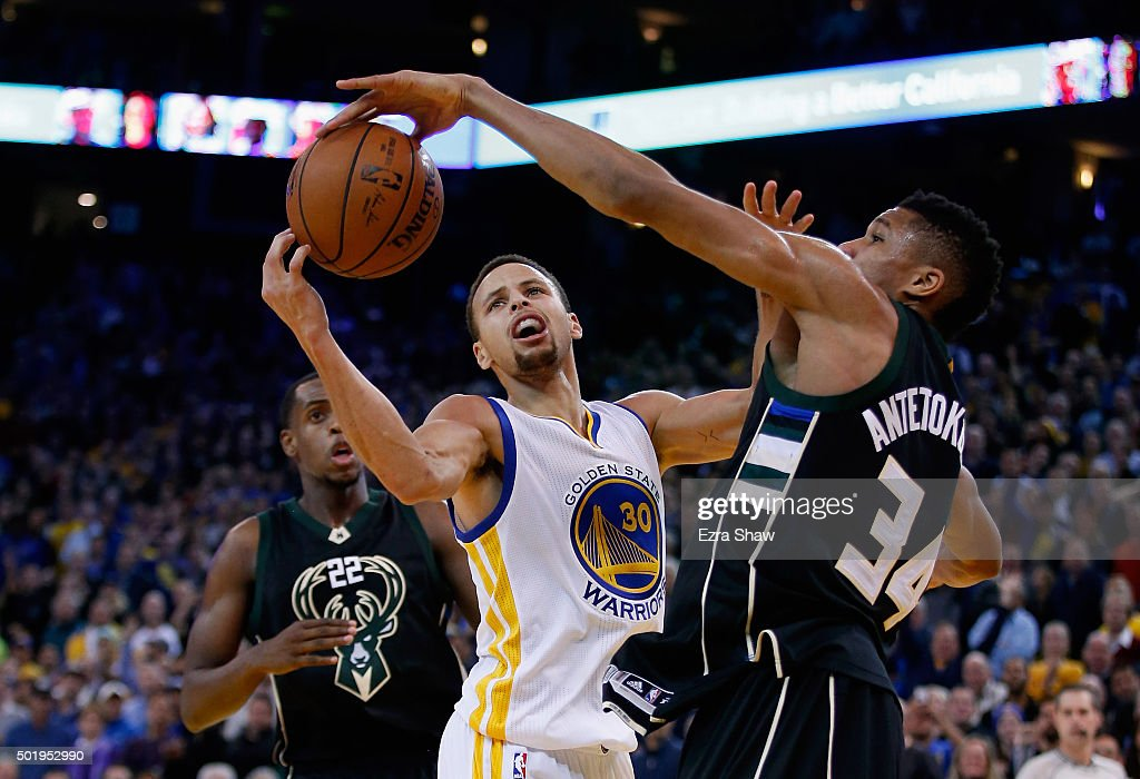 Stephen Curry #30 of the Golden State Warriors and Giannis Antetokounmpo #34 of the Milwaukee Bucks go for the ball at ORACLE Arena on December 18, 2015 in Oakland, California.