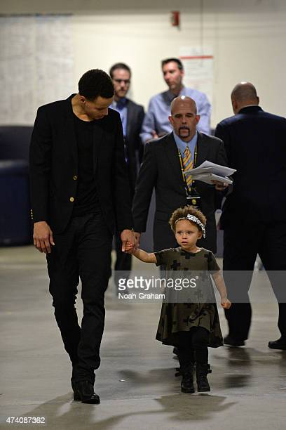 Stephen Curry of the Golden State Warriors and his daughter Riley walk toward to the post game press conference after the game against the Houston...