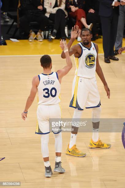Stephen Curry of the Golden State Warriors and Kevin Durant of the Golden State Warriors high five during the game against the Los Angeles Lakers on...