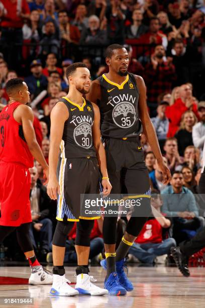 Stephen Curry of the Golden State Warriors and Kevin Durant of the Golden State Warriors look on during the game against the Portland Trail Blazers...