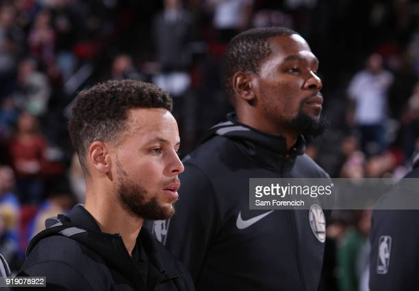 Stephen Curry of the Golden State Warriors and Kevin Durant of the Golden State Warriors look on during the national anthem before the game against...