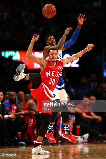 Stephen Curry of the Golden State Warriors and the Western Conference competes for the ball with Paul George of the Indiana Pacers and the Eastern...