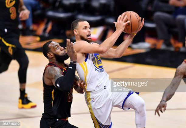 Stephen Curry of the Golden State Warriors attempts a layup defended by LeBron James of the Cleveland Cavaliers in the third quarter during Game...